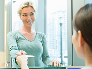 Woman checking in at reception desk