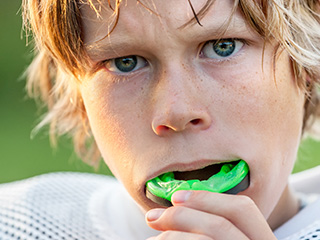Teen boy putting sportsguard in mouth