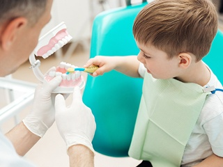 Young boy practicing tooth brushing at dental office