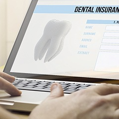 person filling out a dental insurance form on a laptop