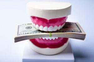 model of teeth biting a stack of money