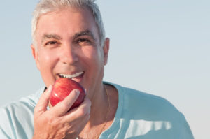 older man smiling eating apple