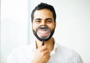 man with magnifying glass in front of smile