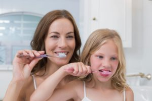 mom and daughter brushing teeth together