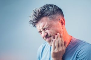 man with toothache who needs emergency dentist in Edison