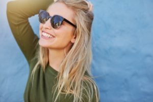 Healthy woman with sunglasses smiles after visiting Edison cosmetic dentist